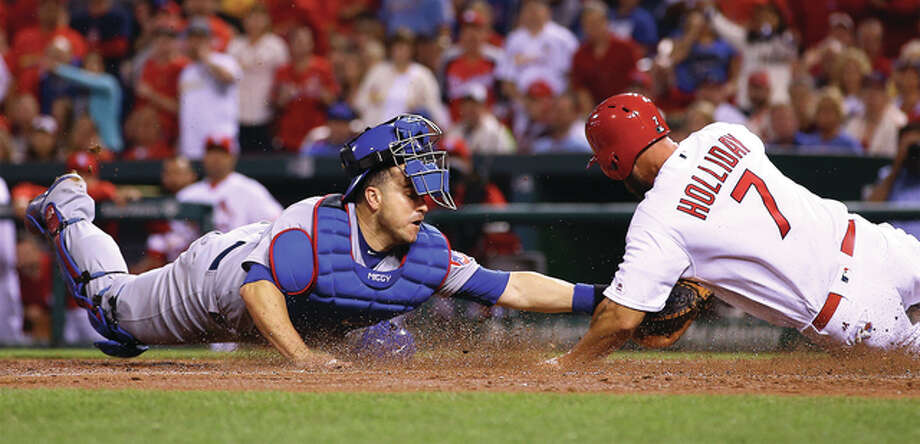 The Cardinals' Matt Holliday (7) is tagged out at the plate by Cubs catcher Miguel Montero after tagging from third base on a flyball in fourth inning of Tuesday's game at Busch Stadium. Photo: Billy Hurst / For The Telegraph