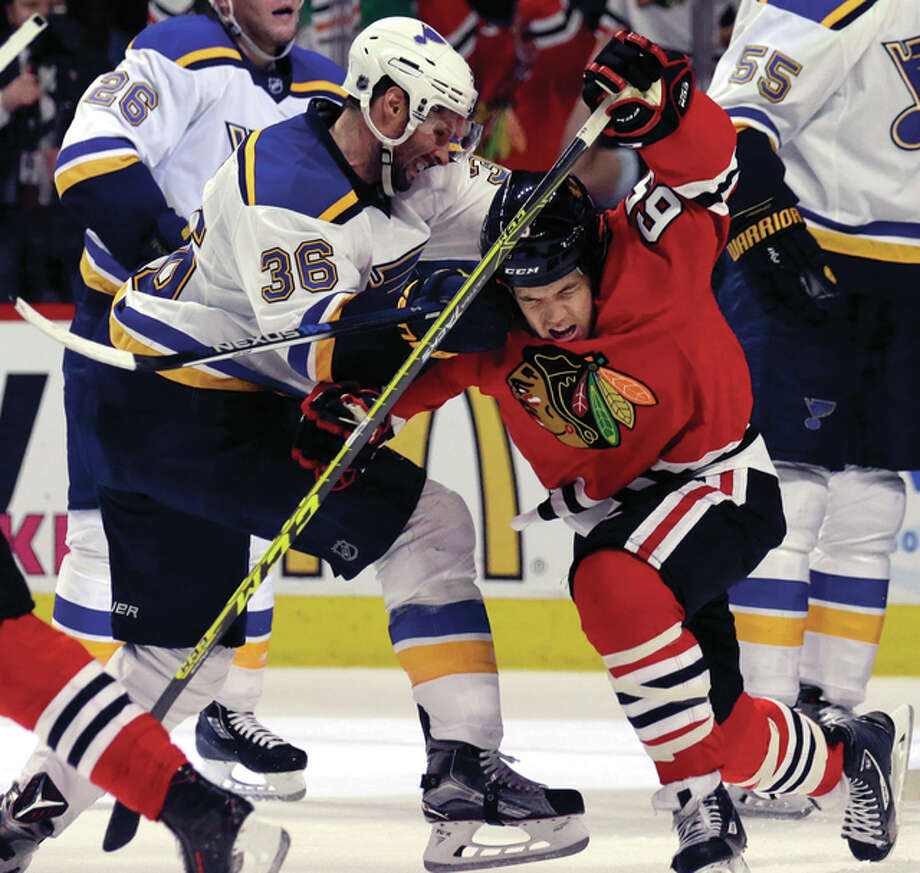 The Blackhawks' Andrew Shaw (right) gets knocked down by the Blues' Troy Brouwer (36) as Shaw tries to skate off to celebrate with his teammates after Chicago goal during the second period in Game 4 on Tuesday night in Chicago. Photo: Associated Press