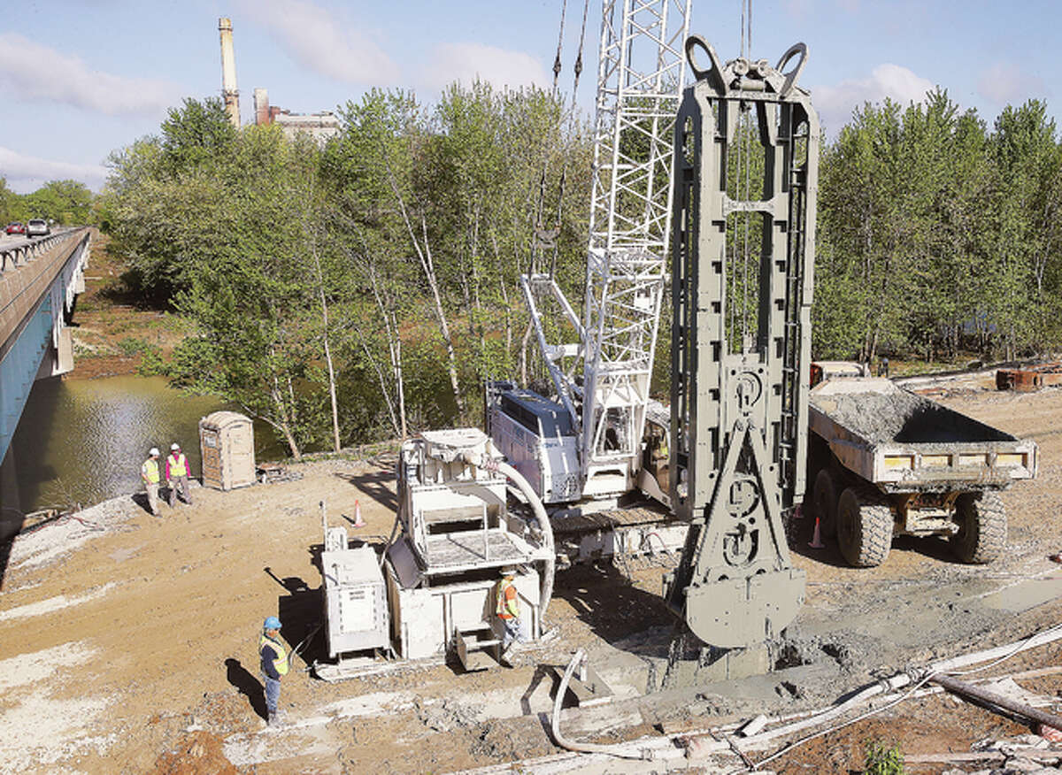 A large crane-lifted device is pulled from a hole where it chomped out more slurry adjacent to Wood River Creek, left, along Illinois Route 143 in East Alton Friday. The work is part of erecting a wall, underground, to line the edges of the levee system at the mouth of the creek where it meets the Mississippi River. The work will prevent seepage of floodwater through the levee.
