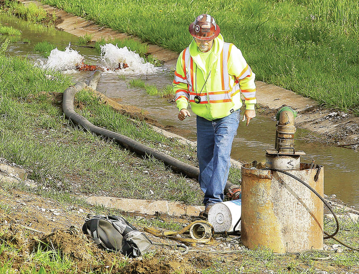 Water is pumped from a relief well along the north side of Illinois Route 143 in Alton as a worker checks on the progress Friday. A series of new relief wells have been installed as part of the massive overall project to upgrade the levee system.