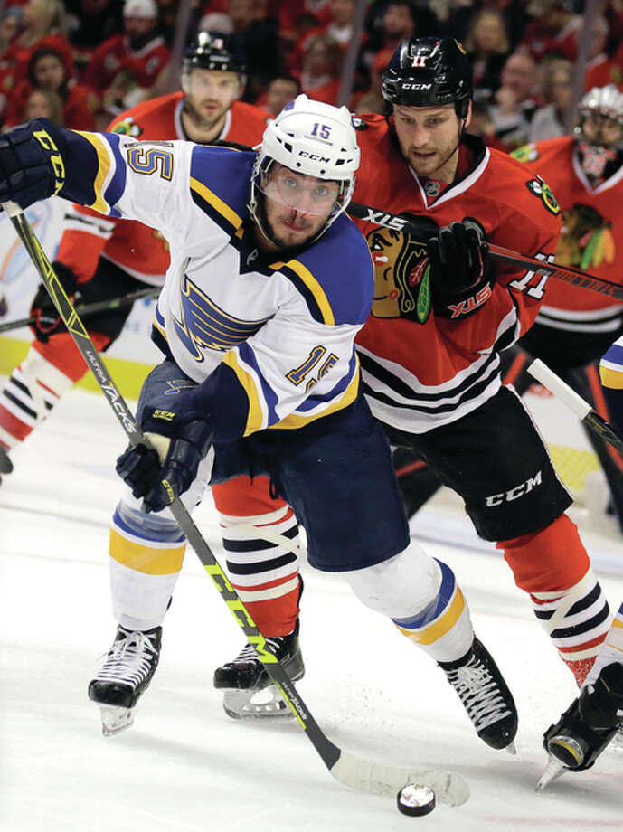 The Blues' Robby Fabbri (front) passes the puck with the Blackhawks' Andrew Desjardins pursuing the play during the first period in Game 6 of a NHL first-round playoff series Saturday night in Chicago. Photo: Associated Press