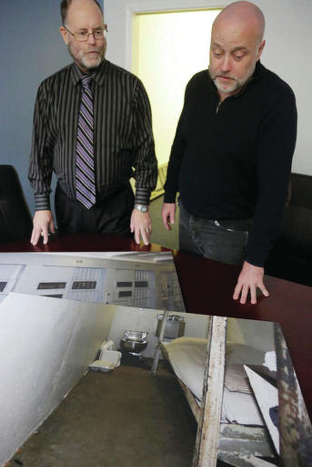 In this April 21 photo, Brian Nelson, right, prisoners' rights coordinator, and Alan Mills, executive director of the Uptown People's Law Center, look at photos of Nelson's former cell at Illinois' Menard Correctional Center. Nelson served years in prison for armed robbery and murder, many of which were in solitary. Illinois lawmakers are pushing state prisons to restrict their use of solitary confinement, joining a national movement that has policymakers rethinking a decades-old punishment that critics say has deep psychological impacts.