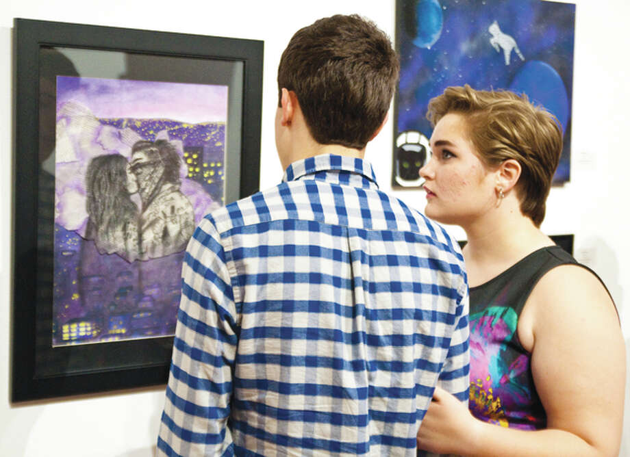 "Boston Perry and Sam Smith take the their time to look at a piece of mixed media artwork by Edwardsville junior Rebecca Lyn entitled ""Forbidden Love"" on Sunday evening at the Jacoby Arts Center, which hosted the Regional High School Art Exhibit Awards Ceremony sponsored by the Illinois American Water Company."