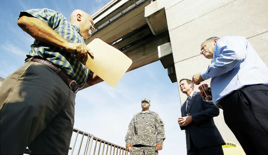 Lou Dell'Orco, left, Chief of Operations for the Melvin Price Locks and Dam 26 in Alton, talks to, from left: Col. Anthony Mitchell, U.S. Army Corps of Engineers; U.S. Rep. Rodney Davis, R-Taylorville; and U.S. Rep. Mike Bost, R-Murphysboro, Tuesday morning at the base of the dam. Both Bost and Davis are members of the House Committee on Transportation and Infrastructure and were gathering input on dam needs in advance of the reauthorization of the Water Resources Development Act. Photo: John Badman | The Telegraph