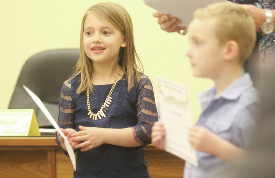 Scott Cousins/The Telegraph Kaylea Falk, a kindergarten student at Bethalto East Primary School, holds her certificate of recognition she received at the Bethalto school board meeting Monday for her participation in the Young Author's Contest.