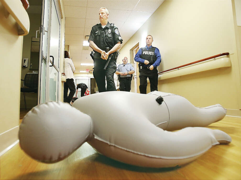 "Alton police officers and Alton Memorial Hospital security officers move cautiously as they check rooms in the hospital's surgical wing Wednesday morning during an ""active shooter"" drill held at the hospital. The inflatable dummy represents one of three victims found by police as they practiced the security drill and police sought the gunman. Since there are always patients in the hospital, police pretended to be holding their rifles or used their fingers to represent their hand guns."