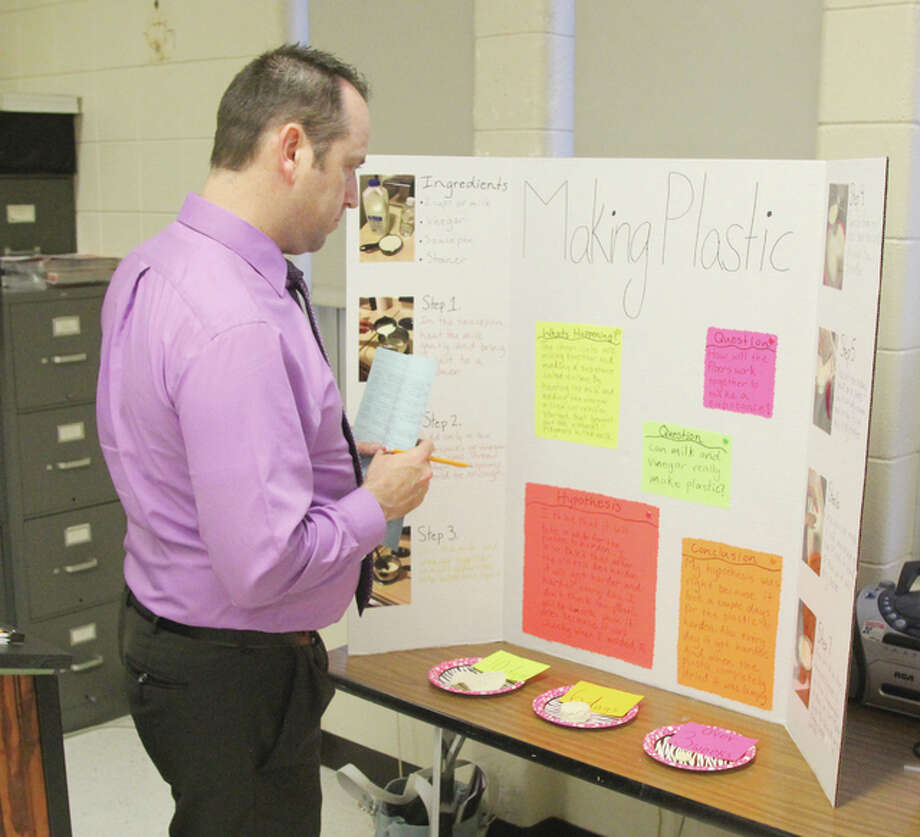Parent James Knapp looks over a project on making home-made plastics at a science fair held Tuesday at Lewis and Clark Jr. High School in Wood River. This was the first science fair held at the school in approximately 20 years, according to organizers.