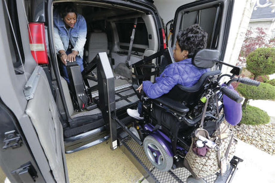 Elaine Walker helps her daughter, Melissa, into the car at their home in South Holland on Thursday. Illinois Gov. Bruce Rauner is cutting costs in a state budget crisis by limiting overtime worked by home care workers. That would include providers such as Walker,who cares for her daughters, Melissa and Dasia, both with cerebral palsy.