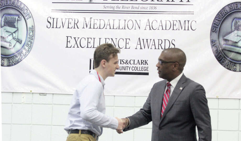 Alton High School senior Matthew Butler is congratulated by Superintendent Kenneth Spells at the 28th annual Silver Medallion Academic Excellence Awards Banquet, held Thursday at Lewis and Clark Community College. The annual event honors the top 8 percent of students in area schools.