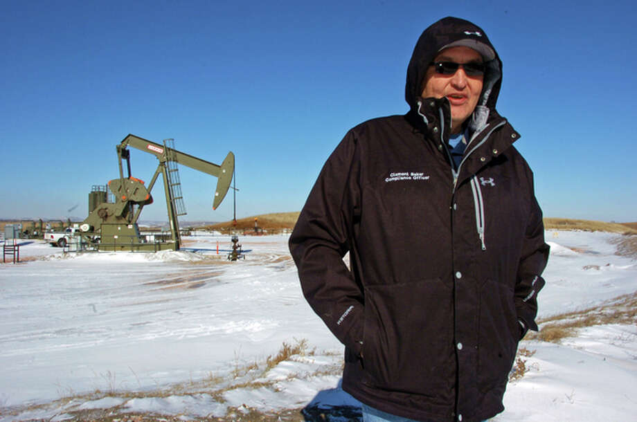 In this Feb. 25, 2015 photo, Clement Baker, a compliance officer for the Three Affiliated Tribes Environmental Division, is seen during an inspection of oil and gas production operations near Mandaree, N.D. A team led by researchers at the University of Michigan has found that fossil fuel production at the Bakken Formation in North Dakota and Montana is emitting roughly 2 percent of the ethane detected in the Earth's atmosphere. Along with its chemical cousin methane, ethane is a hydrocarbon that is a significant component of natural gas. Once in the atmosphere, ethane reacts with sunlight to form ozone.