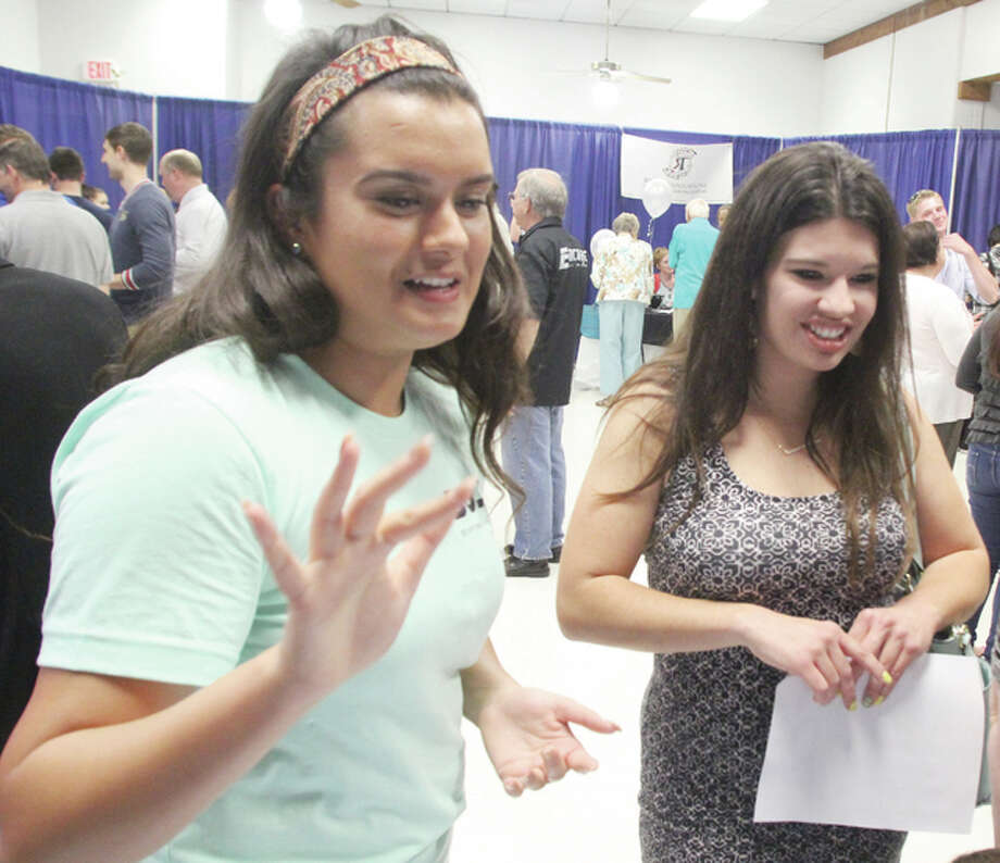 Phebe Bolt, left, a participant in Granite City High School's CEO program, talks about her clothing business with Riverbend CEO facilitator Katie McBee at a CEO Trade Show Wednesday at the Sam Wolfe Granite City Campus of Southwestern Illinois College. As part of the program, students create their own business. Photo: Scott Cousins | The Telegraph