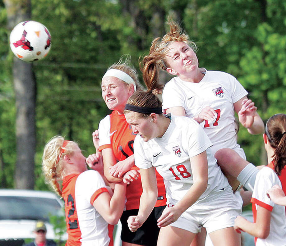 Alton's Annie Evans (17) goes high to score goal on a head ball off a corner kick by teammate Bri Hatfield against Edwardsville Tuesday at Alton High. Also pictured is Alton's Sydney Mossman (18), who later scored to tie the game 2-2. Edwardsville rallied with a goal less than a minute later to grab a 3-2 win. Photo: James B. Ritter | For The Telegraph