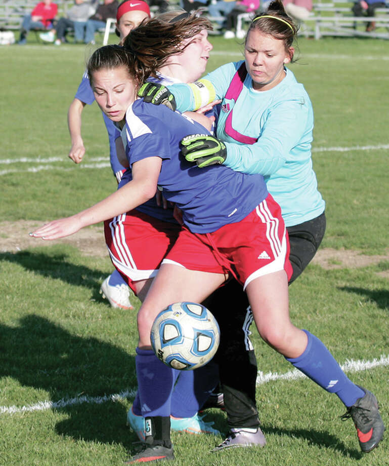 Carlinville's Gabby Marchiori, front, and McKenzie Michaelis, back, battle for the ball against EA-WR goalie Becca Richards during action earlier this season in Wood River. The postseason begins this weekend for some of the the state's Class 1A girls soccer teams, with all teams seeing action next week. Photo: James B. Ritter | For The Telegraph