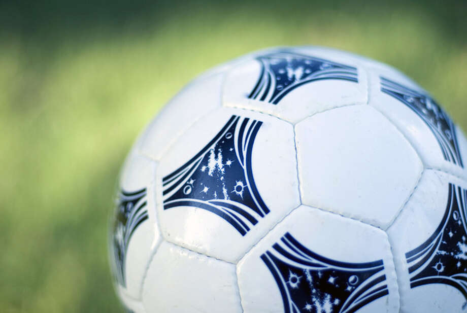 a white and black soccer ball with a green grass background