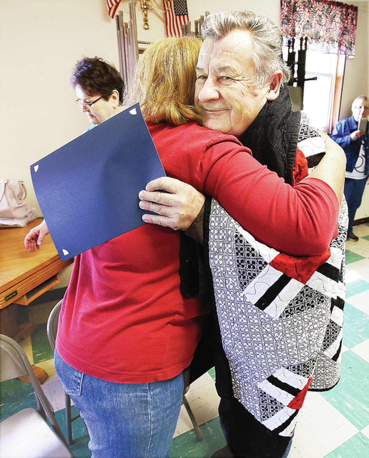 U.S. Army veteran Sgt. Dennis Barnhart gets a big hug from Jan Copeland, with the Quilts of Valor Foundation, at the ceremony Thursday at the Cottage Hills VFW Post.