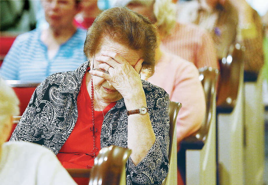 "John Badman|The Telegraph Marge May, of Eden Prairie, Minn., bows her head in prayer Thursday during the National Day of Prayer ceremonies held at United Methodist Village in Godfrey where May was visiting a friend. The chapel at the retirement community was nearly full as people gathered to pray for the military, out country and for peace on earth. Master of Ceremonies Barb Santos reminded people to ""Pray, Act and Love""."