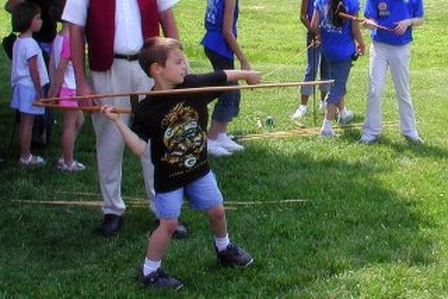 "A child launches a spear with an ""atlatl"" throwing tool at a past Kids Day event."