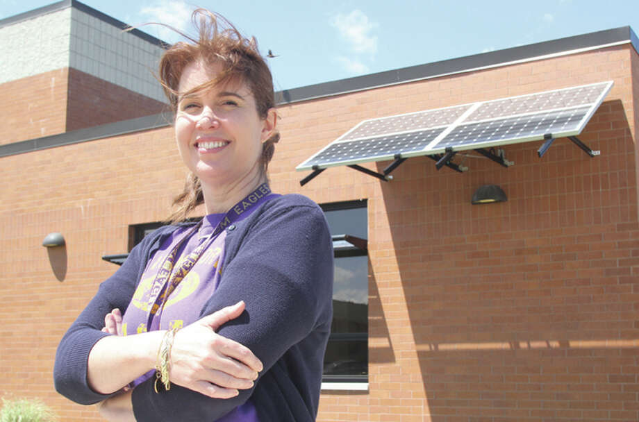 "Suze Gibson, a special education teacher at Civic Memorial High School, stands in front of the new solar panel recently installed at the school. In addition to providing electricity the panels will also be used for educational purposes. A ""solarbration"" promoting the new tool will be from 11 a.m. to 1 p.m. Saturday at the school."