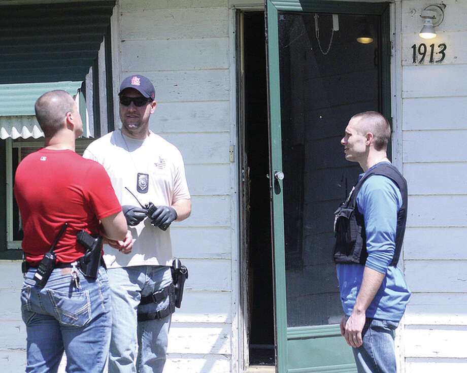 Alton Police Department investigators meet outside the 1913 Alby St. home that was raided by Illinois State Police Friday afternoon following a lengthy narcotics investigation.