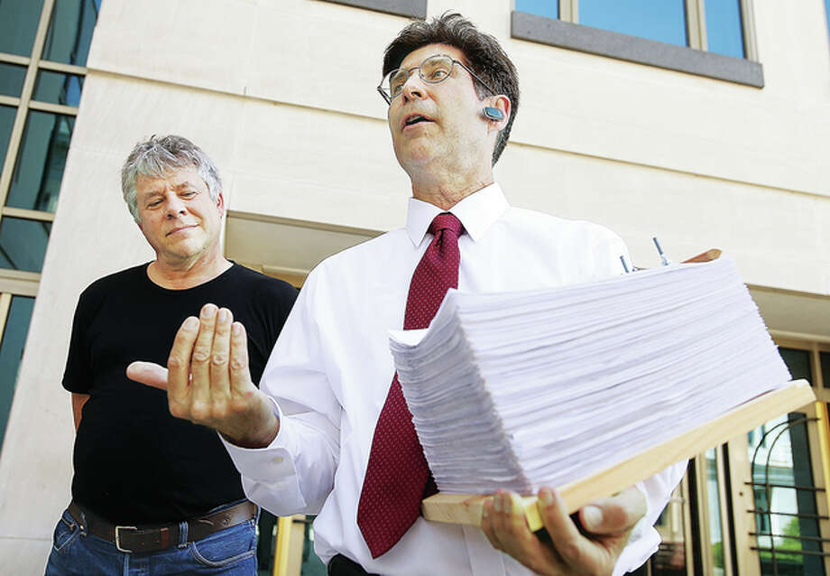 Madison County Treasurer Kurt Prenzler, right, holds some 10,000 signatures of registered Madison County voters that Dr. Mike Firsching, left, an Edwardsville veterinarian, was about to deliver to the Madison County Clerk's Office Friday. The signatures will allow voters to decide in November if they want to reduce the county's ability to levy taxes for its general fund.
