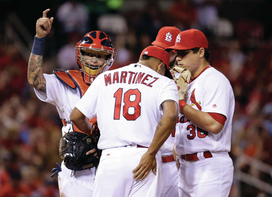 The Cardinals' Yadier Molina (left) calls for a trainer as he stands on the mound with pitcher Carlos Martinez (18) and Aledmys Diaz during the fourth inning against the Pittsburgh Pirates on Friday night at Busch Stadium. Martinez left the game. Photo: Associated Press