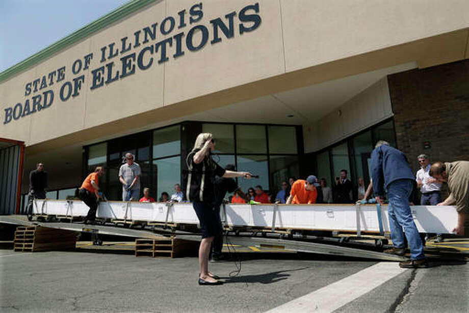 Workers unload signature petitions out of a truck at the Illinois State Board of Election office Friday in Springfield. Backers of taking politics out of how the state draws its political districts delivered the petitions to election officials that will allow a measure to be placed on the November ballot. The group is pushing for the creation of an independent body to draw the maps, and have gathered nearly 600,000 petitions.