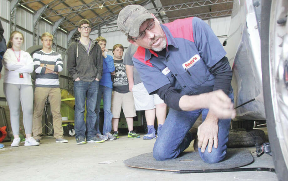 Scott Cousins/The Telegraph Heath Hammann, a lead technician at Andy's Tire And Auto Service in Bethalto, shows a group of driver's ed students at Civic Memorial High School how to change a tire Wednesday. As part of their driver's ed course the class spends a day learning about basic maintenance and repairs, including changing a tire.