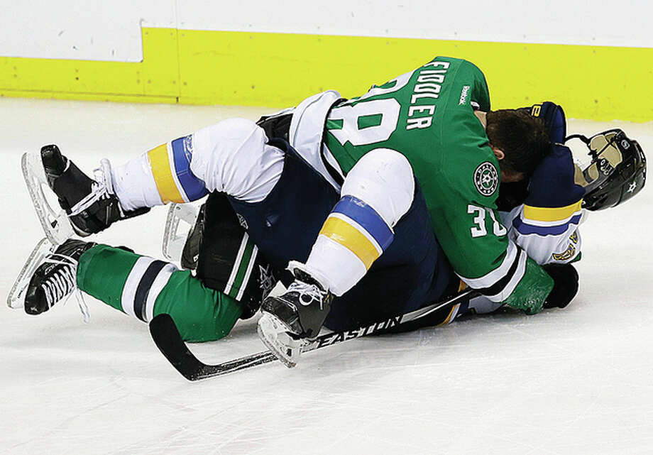 The Stars' Vernon Fiddler and Blues defenseman Kevin Shattenkirk (22) fight in the third period Saturday's game in Dallas.