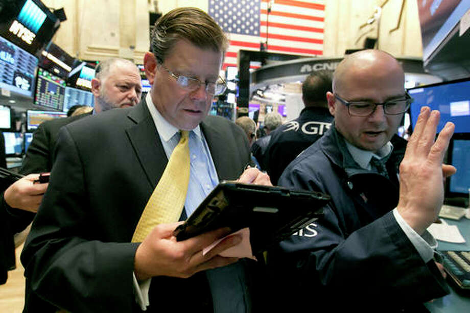 Trader Edward Shreier, center, and specialist Mario Picone, right, work on the floor of the New York Stock Exchange, Friday. Stocks were slightly lower in early trading Friday after a report on the U.S. economy showed a significant slowdown in hiring last month, echoing weakness seen earlier in the week in Europe and Asia.