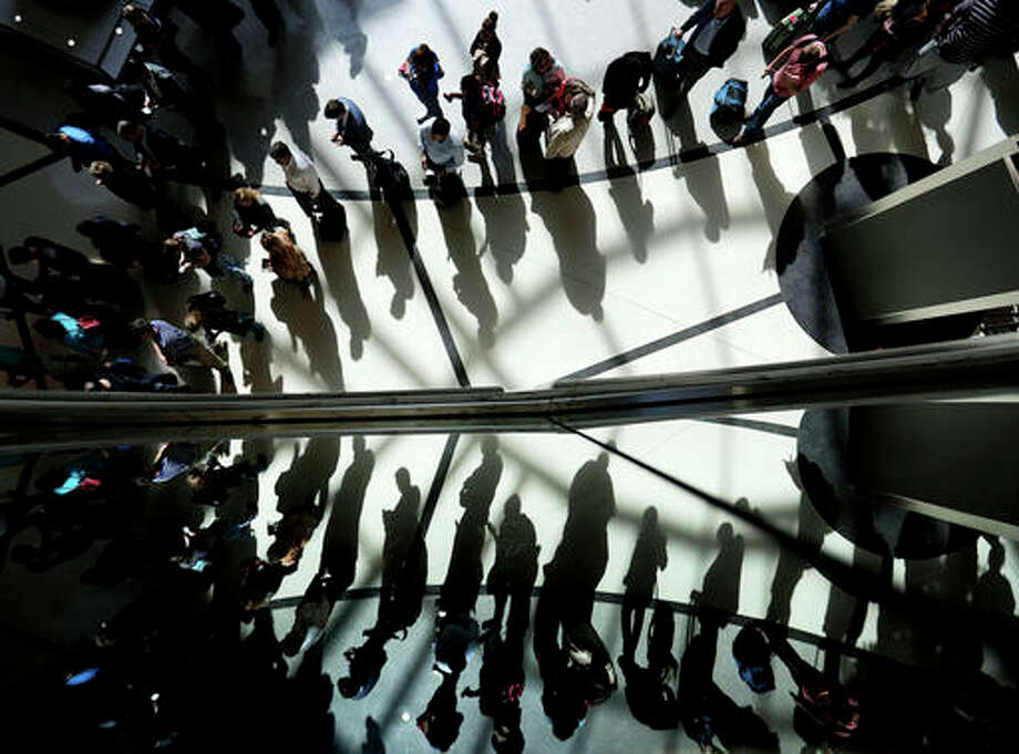 In this Thursday, March 10, file photo, passengers are reflected in glass as they line up to go through a security checkpoint under the atrium of the domestic passenger terminal at Hartsfield-Jackson Atlanta International Airport in Atlanta. Airport security lines have become so bad that airlines themselves are urging passengers to share their frustration with the government on social media. Airlines for America, the industry's trade group, just launched a website called iHateTheWait.com, encouraging fliers to post photos of the lines on Twitter and Instagram along with the hashtag #iHateTheWait.