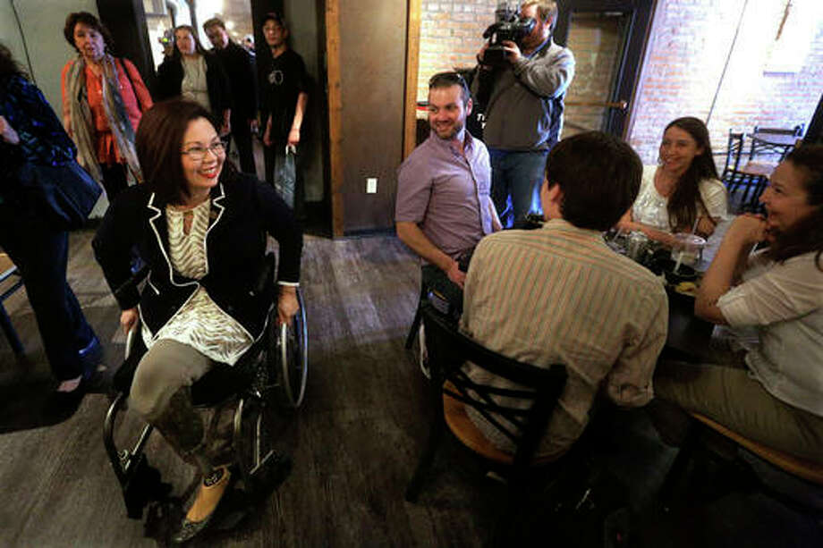 In this March 16 file photo, U.S. Rep. Tammy Duckworth, the Democratic candidate for U.S. Senate, left, greets supporters at a restaurant in Springfield, Ill., a day after winning the state's Democratic primary. Duckworth's record on veterans issues has become a target as she tries to unseat U.S. Sen. Mark Kirk, a former Navy commander, in the November election.