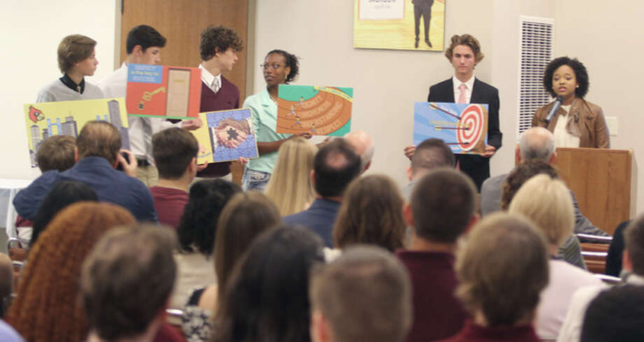 Alton High School students hold up signs that will be used to promote positive change in the school while Anya Jones, right, make a presentation on the school's new Bridges program Thursday as part of the Manny Jackson Center for the Humanities Conversation Toward a Brighter Future program.