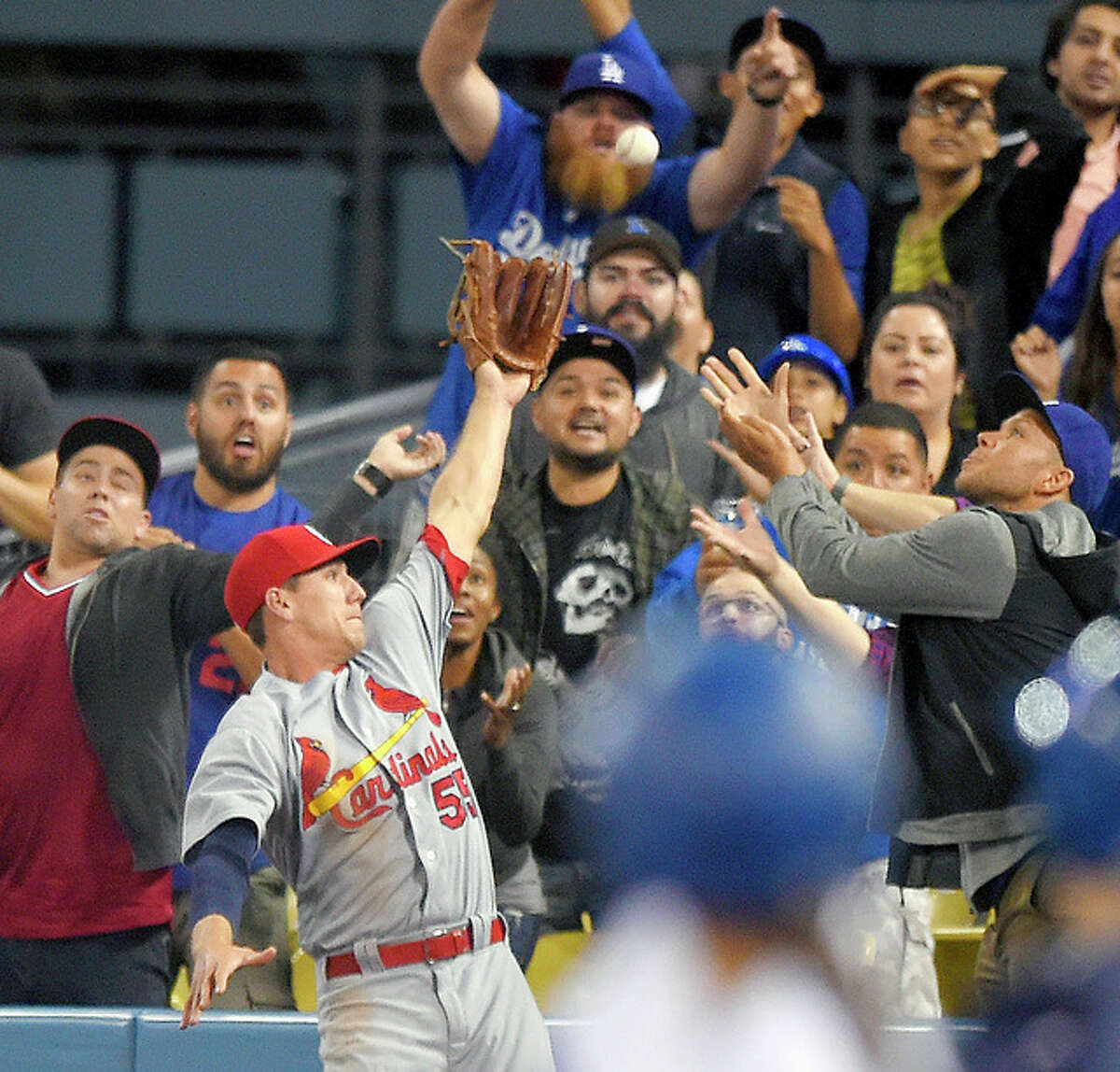 Cardinals right fielder Stephen Piscotty can't reach a ball hit by the Dodgers' Yasiel Puig for a solo home run in the sixth inning of Friday's game in Los Angeles.
