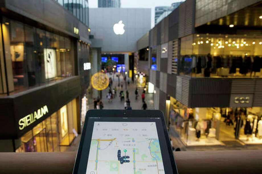 A mobile device displaying the Didi Chuxing app is posed near the Apple store logo in Beijing, China, Friday. Apple Inc. has invested $1 billion in Chinese ride-hailing service Didi Chuxing, the main competitor in China for Uber Technologies Ltd.