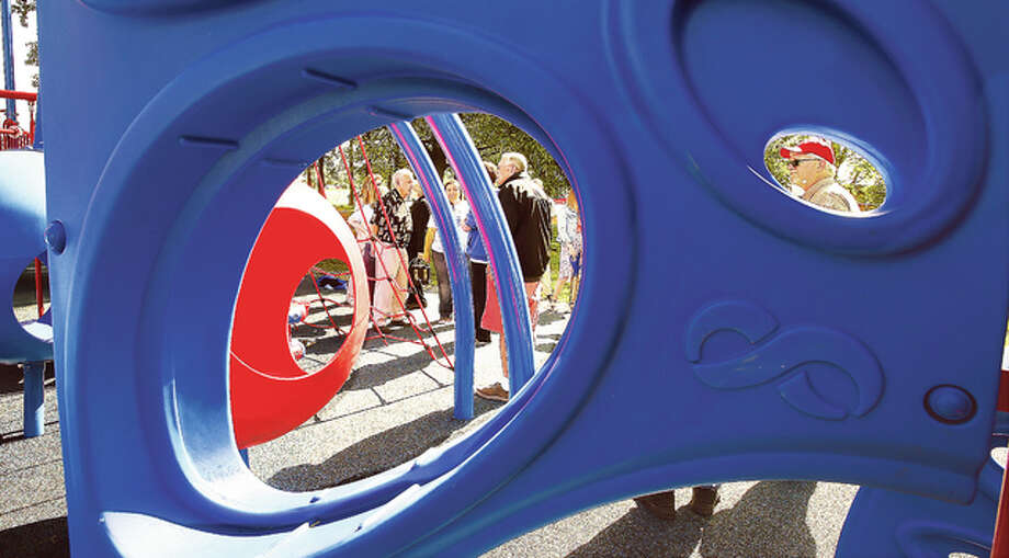Dignitaries get a closer look Friday at the new playground equipment installed in the Godfrey park behind the Godfrey Town Hall as framed through holes in the plastic equipment that makes up part of the playground. The old playground was completely removed from the site.