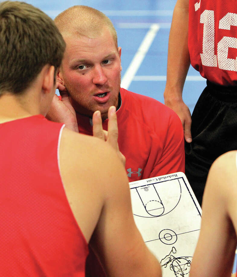 Josh Krumwiede (center) talks with his Staunton Bulldogs boys basketball team during a timeout in a summer tournament last year in Jacksonville. Krumwiede, a Carrollton native, has accepted the jobs as basketball and baseball coach at Dieterich after one year at Staunton. Photo: Dennis Mathes / Journal-Courier