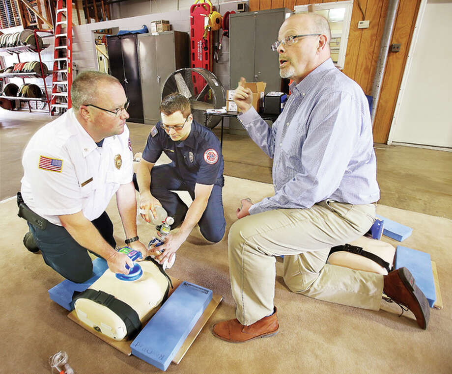 Mark Thurow, right, an EMT-paramedic and clinical educator for Zoll Medical Corp., talks to Godfrey firefighters about the use of their new ResQCPR system, being practiced, left. The Godfrey Fire Protection District is the first fire department in the state to start using the new system, which improves the efficiency of CPR. The system is made up of two parts, the ResQPUMP which attaches to the victim's chest, left, and allows a lifting force in addition to the traditional downward pressure of CPR. The other component, the ResQPOD, center, which is attached to the ventilator, prevents the influx of unnecessary air through the patient's airway. When the U.S. Food and Drug Administration-approved devices are used together, they improve the likelihood of one-year survival after cardiac arrest by 49 percent. Photo: John Badman | The Telegraph