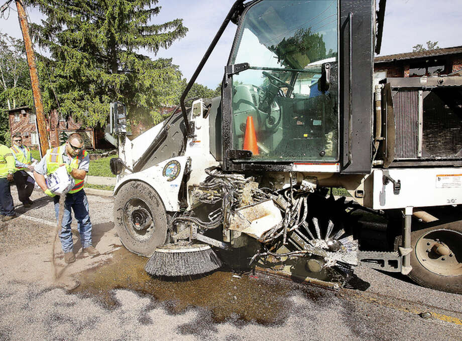 Alton Public Works employees spread oil-dry to absorb gallons of hydraulic fluid leaking Wednesday from the 2014 Elfgen street sweeper that was struck by a truck hauling a small tractor while it was sweeping in the 800 block of Washington Avenue. The truck and trailer, from GLC on Seminary Street in Alton, left the scene but was followed by another city vehicle until police could stop it on the Crpl. Chris Belchik Memorial Expressway, just north of Illinois Route 143. The sweeper was struck in the most sensitive and expensive part of the vehicle, destroying hydraulic operations. Fred's Towing in Alton had to haul the sweeper away, and the driver was not injured.