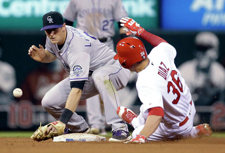 The Cardinals' Aledmys Diaz, right, is safe at second on a double as the throw gets away from Colorado Rockies second baseman DJ LeMahieu in the sixth inning Wednesday night's game at Busch Stadium. Photo: Jeff Roberson | AP Photo