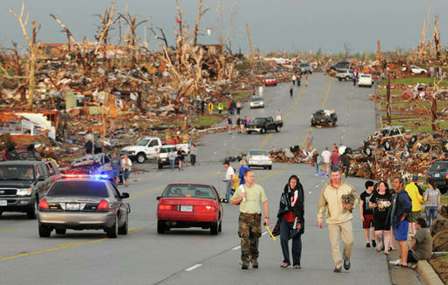 In this May 22, 2011, file photo residents walk in the street after a massive tornado hit Joplin, Mo. A sky-darkening storm was working its way into southwest Missouri around dinnertime on a Sunday evening of May 22, 2011, zeroing in on the city of Joplin. As storm sirens blared, one of the nation's deadliest tornados hit, leveling a miles-wide swath of Joplin and leaving 161 people dead. Photo: AP Photo/Mike Gullett, File