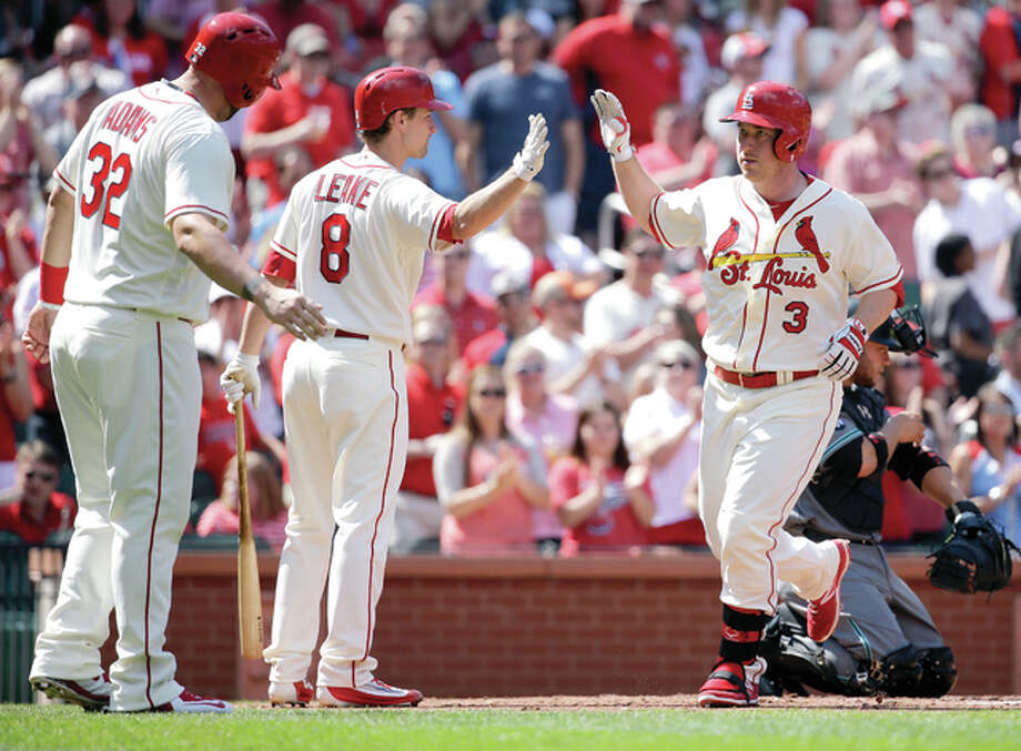 The Cardinals' Jedd Gyorko, right, is congratulated by teammates Mike Leake and Matt Adams, left, after hitting a two-run home run in the second inning Saturday against the Arizona Diamondbacks in St. Louis. Photo: Jeff Roberson | AP Photo