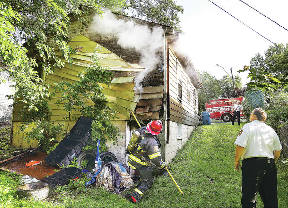 A fire that started outside of a residence in the 2700 block of Viewland Street in Alton Monday morning, burned through a rear corner of the house making the siding fall off easily and in a large chunk, as firefighters overhauled the fire. No one was injured due to the fire. Photo: John Badman|The Telegraph