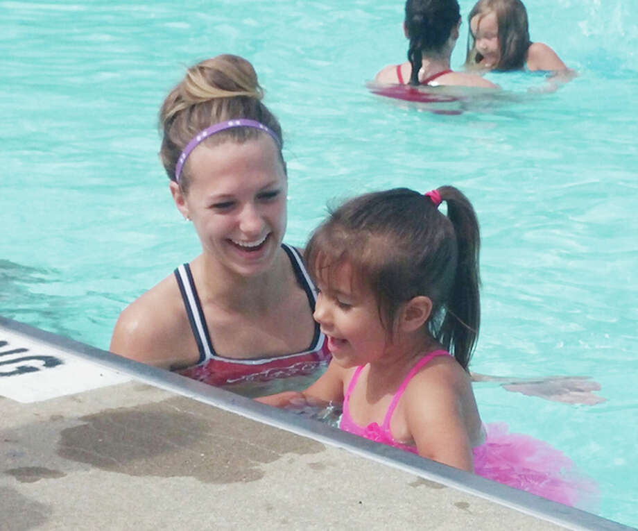 Raelyn Sinclair receives Level 1 instruction by Kellie Phipps on the first day of swim lessons during the 2015 season.