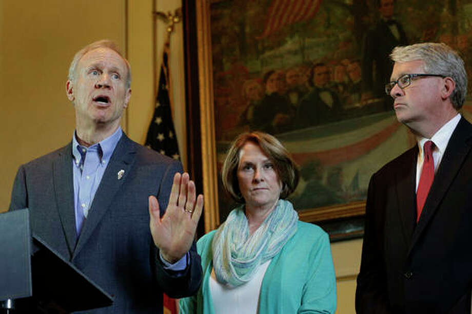 Bruce Rauner speaks to reporters in his office at the Illinois State Capitol in Springfield, Ill. Looking on is Illinois Senate Minority Leader Christine Radogno, R-Lemont, center, and Illinois House Minority Leader Jim Durkin, R-Western Springs, right.