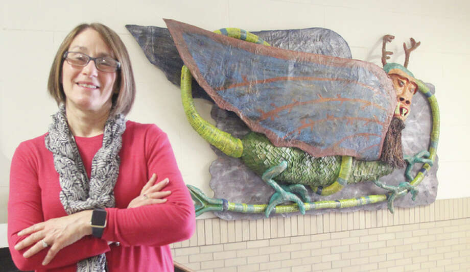 Retiring Alton Middle School art teacher Mimi Almonroeder stands in front of a paper mache version of the Piasa Bird that students made over the last school year. About 50 students in four separate classes worked on the project. Photo: Scott Cousins/The Telegraph