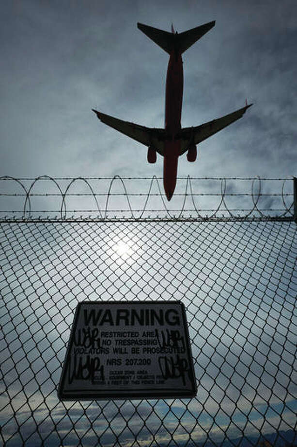 In this May 17, 2016, photo, a sign warns against trespassing as a plane lands at McCarran International Airport in Las Vegas. An Associated Press investigation has documented perimeter breaches at many of the busiest airports in the U.S.