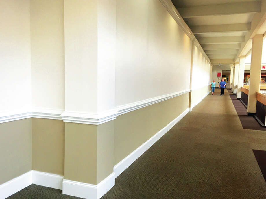 A pair of walkers stroll through the upper level of Alton Square Mall on Thursday afternoon. Hull Property Group, the mall's owner, recently installed drywall and crown moulding to hide empty storefronts and improve the aesthetic. Photo: Kelsey Landis   The Telegraph