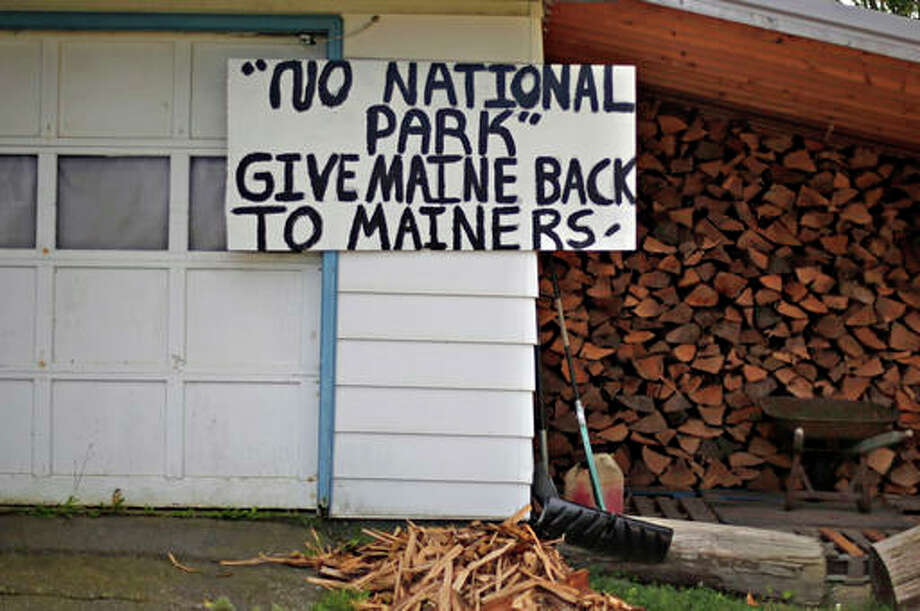 In this Sunday, Aug. 9, 2015, file photo, a sign in opposition to a proposed national park is seen on a home in Millinocket, Maine. The former Great Northern Paper Co. mill closed in February 2013, devastating the Katahdin region economy. A congressional field hearing this week on a proposal to create a national monument shows how the lines have been drawn.