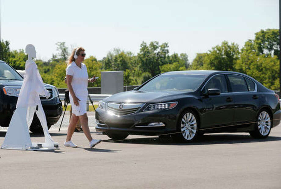 In this July 20, 2015 file photo, a pedestrian crosses in front of a vehicle as part of a demonstration at Mcity, used to test driverless and connected vehicles, on the University of Michigan campus in Ann Arbor, Mich. The U.S. auto industry's home state of Michigan is preparing for the advent of self-driving cars by pushing legislation to allow for public sales and operation _ a significant expansion beyond an existing law that sanctions autonomous vehicles for testing only.