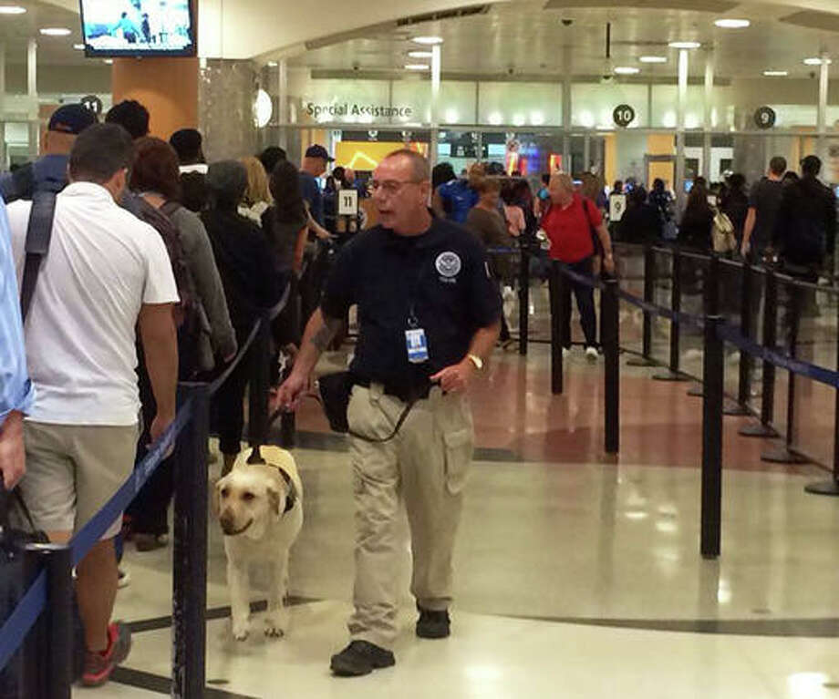 A K-9 unit checks travelers in line to enter the main security gate at Hartsfield-Jackson Atlanta International Airport, Friday, May 27, 2016. Memorial Day weekend, the unofficial start of summer vacations for many and a busy travel period, serves as a crucial test for the TSA agency.